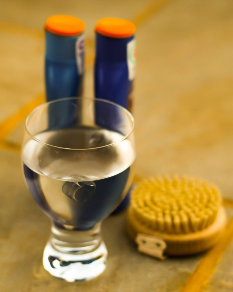 sunscreen, glass of water and scrubbing brush for blog on skin tanning damage