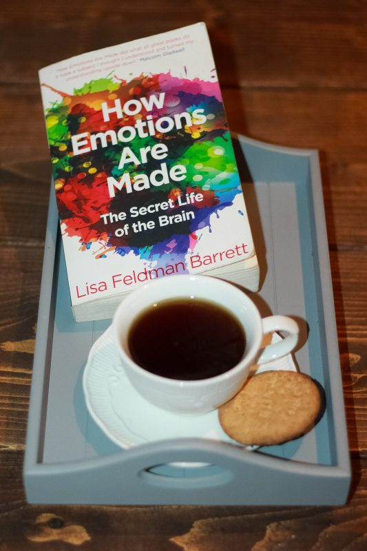 Book How Emotions Are Made with coffee and biscuit - nonfiction books that make you smart