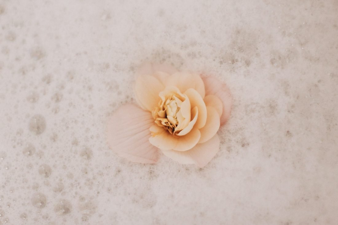 image of white flower in bubble bath for post on how to stop loving someone