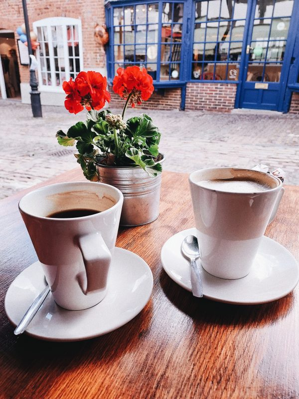 Image of two coffee cups at outdoor cafe for blog on how much to tell your partner about your friends